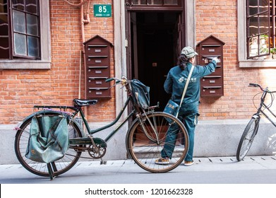 SHANGHAI, CHINA - DEC 1: a 'China Post' postwoman delivers mail by bicycle to a private residence in Shanghai, China on December 1, 2010
