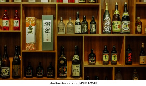 Shanghai, China - Dec 11 2015: Kamotsuru Itteki Nyukon, Takara Sho Chiku Bai Classic Junmai, Nihonsakari various brands of Sake (Japanese rice wine) bottles on shelves in izakaya styled restaurant.
