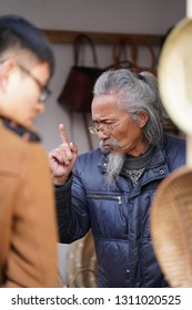 Shanghai, CHINA - Dec 15, 2018: One old man persuading the tourists to buy his goods
