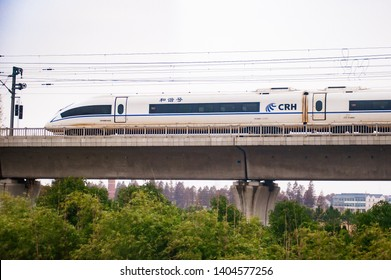 SHANGHAI, CHINA - DECEMBER 01, 2012: Highspeed G train across the city with buildings and trees on the background