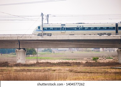 SHANGHAI, CHINA - DECEMBER 01, 2012: Highspeed D train across the field with buildings and smog on the background