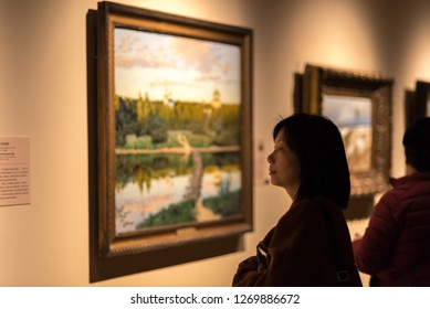 Shanghai, China - December 2017: Asian woman, museum visitor looking at a framed painting on display, art exhibition at Shanghai Museum, blurred background, selective focus