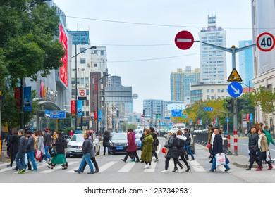 SHANGHAI, CHINA - DECEMBER 25, 2017: Crowd of people walking at crosswalk on the Shanghai city street, China