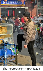 Shanghai, China - February 13, 2013: A Uighur man & his bicycle vending vehicle laden with leaven 'nan' bread. Many Uighurs originally from southwest China, are involved in street side food trade.