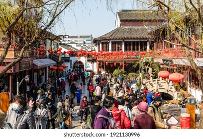 Shanghai, China - February 19, 2021: View of Old Street with massive tourists in face masks, traditional buildings, shops, stores, snack bars, restaurants in Qibao Old Town, Minhang, Shanghai.