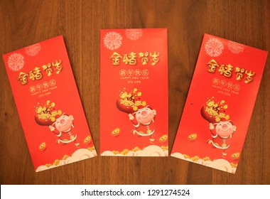 Shanghai / China - January 20th 2019: Red Chinese envelops over wooden table background for celebrating Chinese New Year - year of the pig