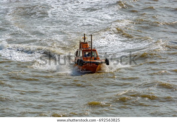 SHANGHAI, CHINA - January 24, 2017: Chinese pilot boat arrives to collect pilot from ship at Yellow sea near Shanghai