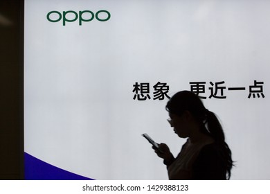 Shanghai, China - June 14, 2019: A woman holding a smartphone walks past an OPPO billboard at a metro station. OPPO is a Chinese consumer electronics and mobile communications company.