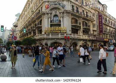 Shanghai, China - June 14, 2019: Shoppers crossing the street in front of the vintage Shanghai Fashion Store on Nanjing Road in Shanghai's old downtown district.