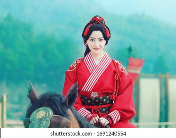 shanghai, china- March 16, 2020: chinese actress Jing Tian wears red traditonal chinese wedding dress Riding on a horse