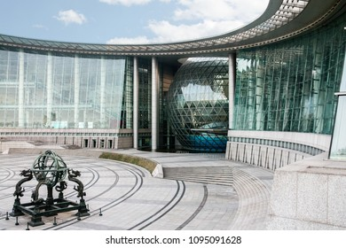 SHANGHAI, CHINA - March 21, 2012: Shanghai science and technology museum with an antique earthquake forecast equipment in front of the entrance of the modern building complex.