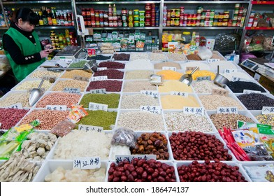SHANGHAI, CHINA - MARCH 22: woman sells products in small grocery shop with seeds at food market on Old City area on March 22, 2013 in Shanghai