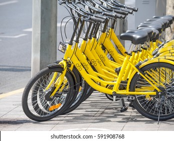 Shanghai, China - March 3, 2017:  Rows of bicycles are placed on the side of the road in Shanghai. Ofo Bikes is a bike sharing company in China.