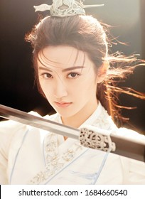 shanghai, china- March 6, 2020: chinese actress Jing Tian wears white ancient Chinese dress drawing a sword