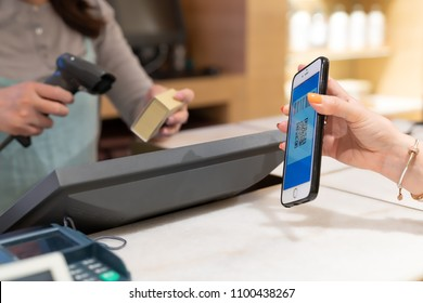 SHANGHAI, CHINA - MAY, 2018 : Qr code payment , online shopping , cashless technology concept. women hand hold the smartphone for payment at shopping center