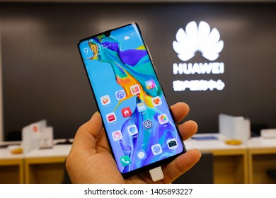 Shanghai, China - May 22, 2019: consumers try out huawei P30 mobile phone at huawei customer service center. Huawei is a world famous telecommunication equipment manufacturer.