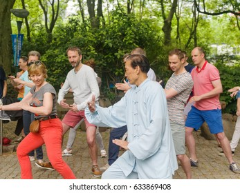 Shanghai, China - May 5,2017: Chinese Taiji Master teaches a group of Belgium tourists how to play Taiji in a park.