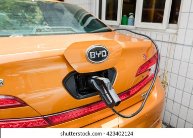 Shanghai, China - May 6, 2016: Power supply for China BYD electric car charging. Electric car charging station. Close up of the power supply plugged into an electric car being charged.