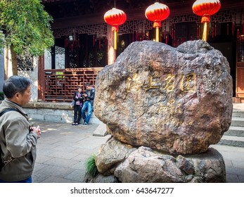 Shanghai, China - Nov 4, 2016: In Yu Yuan (Yu Garden) – Focus of image on boulders with calligraphic Chinese characters or pictogram inscriptions. A man standing-by admiring the text.