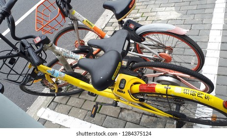 Shanghai, China -  November 15 2018: Yellow and red bicycles with black seats for hire with electronic transaction technology (hire bikes) to prevent traffic congestion and allow ease of transport