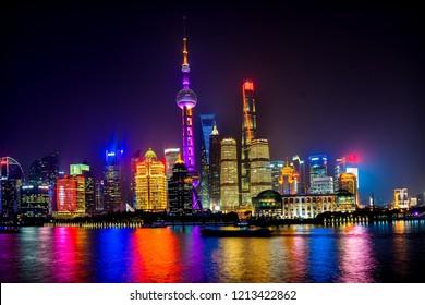 SHANGHAI, CHINA - NOVEMBER 16, 2017 Oriental Pearl TV Tower Pudong Boats Reflections Nights Lights Huangpu River Three Skyscrapers Cityscape Shanghai China