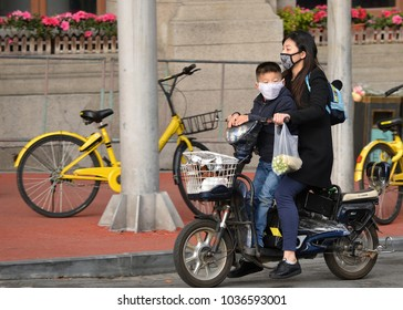 Shanghai, China - November 18, 2017:  Chinese woman and boy, wearing masks, ride a motorized bike on the streets of Shanghai.