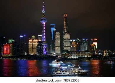 Shanghai, China - November 18, 2017:  Night shot of the magnificent skyline of Shanghai Pudong area with lit tour boats in the Huangpu River.