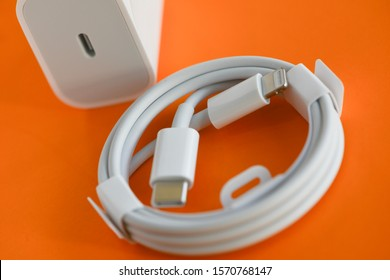 Shanghai, China: November 19, 2019: Brand new USB-C type to Lightning fast charging cable of Apple Inc. on bridge stylish orange background. Charger provides 18W capacity and included with iPhone 11.