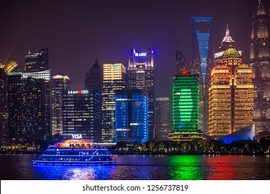 Shanghai, China - October 15, 2018:  A tour boat cruises at the Huangpu River of Shanghai with beautiful cityscape night view at the background.