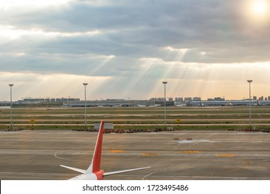 Shanghai, China- October 22 2019 : An air plane is parking in Aircraft Parking in the Pudong airport. In background, there are sun light with many lines of orange sun ray. It's a cloudy and sunny day