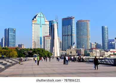 Shanghai, China - October 31, 2017:  People walk along the observation deck of The Bund.  The Monument to the People's Heroes and various buildings can be seen in the background.
