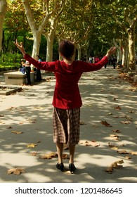 Shanghai/ China - October 8th 2018: Old Chinese Woman dancing in Fu Xing Park on a sunny autumnal morning in the dappled light of trees
