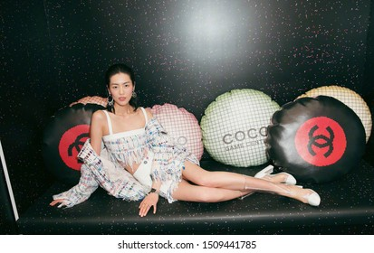 shanghai, china- september 12, 2019: Famous Chinese super model liu wen is wearing CHANEL dress lying on black sofa with coco CHANEL pillows, sexy and pretty Chinese woman