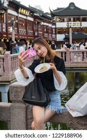 Shanghai, China: September 26, 2018:  A girl takes a selfie at the Old City of Shanghai, China.    Shanghai is the largest city in China and second most populated city in the world.