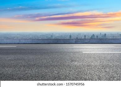 Shanghai city skyline and empty asphalt road scenery at sunset.