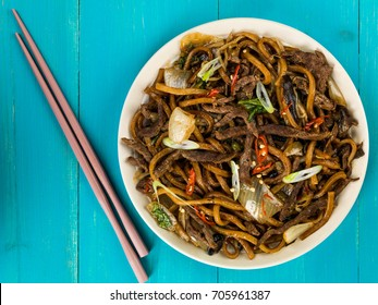 Shanghai Fried Beef and Udon Noodles Against A Blue Wooden Background