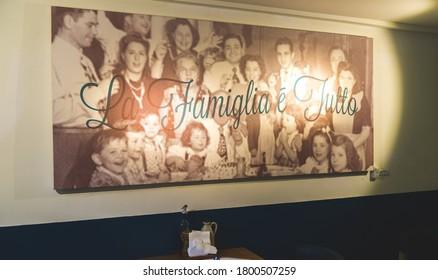 "Shanghai - June 13, 2018: ""La Famiglia Tutti"" photo on the wall, big massive decoration of Italian family, simple modern cafe restaurant, interior design of an Italian restaurant"