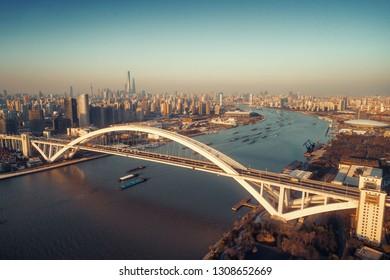 Shanghai Lupu Bridge aerial view over Huangpu River at sunset in China