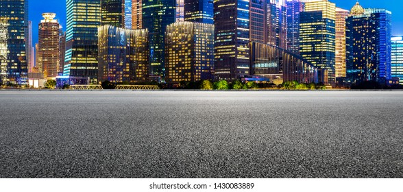 Shanghai modern commercial buildings and empty asphalt road at night