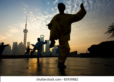 SHANGHAI - NOV 21:  People practice Taiji at the Bund, Oriental Pearl Tower in the background on November 21, 2010 in Shanghai, China.  The tower is one of the top ten Shanghai attractions.