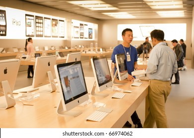 SHANGHAI - NOV 30: A young Apple sales assistant talks to a customer next to iMacs in the Apple store interior shop in Shanghai on Nov 30, 2010.