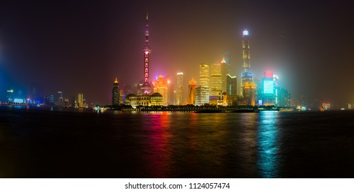 Shanghai skyline glowing in a misty night, reflecting in Huangpu river