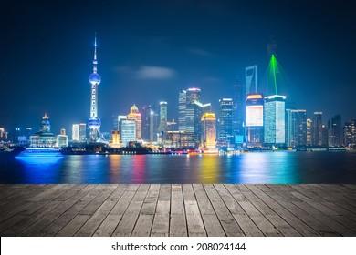 shanghai skyline at night , light show with wooden floor prospect
