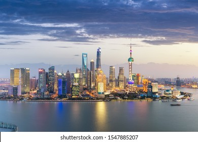 shanghai skyline in nightfall, futuristic pudong financial center and beautiful huangpu river, China.
