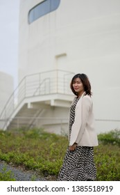 Shanghai/China-April 2019: pretty smiling asian woman standing in front of TANK Shanghai museum. The museum was transformed from decommissioned oil storage tanks. New landmark in Shanghai