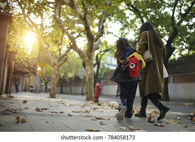 Shanghai,China-December 22,2017:mother and daughter walking on the shanghai street in fall season