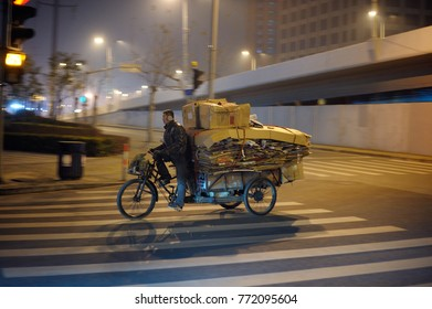 SHANGHAI,CHINA-FEBRUARY 03, 2015: Man on old three wheeler transporting by night used cardboards to the recycling center in Shanghai.