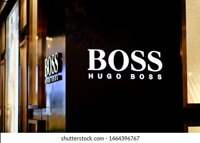 Shanghai/China-July 2019: close up illuminated HUGO BOSS's logo on the wall outside store at night. Blurred side wall with logo and bright advertising board. A German luxury brand focusing on suit