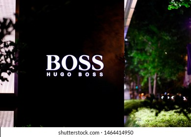 Shanghai/China-July 2019: close up illuminated HUGO BOSS's logo on the wall outside store at night. Blurred green plants and street lights . A German luxury brand focusing on suit