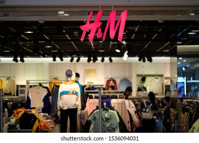 Shanghai/China-Oct.2019: Facade of H&M clothing store. Bright red logo hanging on entrance. Blur clothing store and customers as background. A Swedish fashion brand